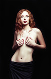 Dramatic studio portrait of sexy redhead girl