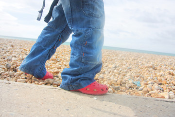 close up shot of child walking along beach wall