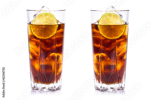 Cola in tall glasses with ice cubes and lime over white