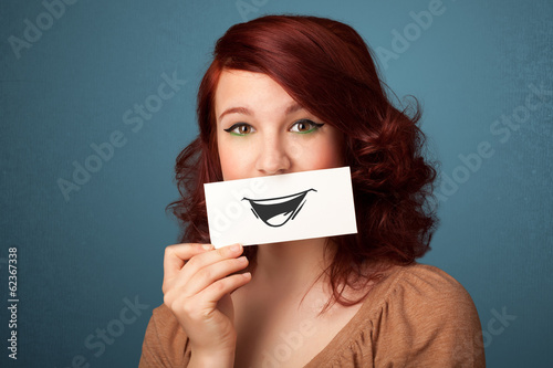 Happy cute girl holding paper with funny smiley drawing