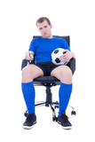 bored man in uniform with remote control watching soccer game is