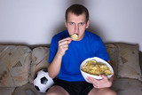 supporter in uniform watching football on tv at home and eating