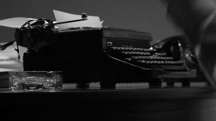 Man typing on a vintage 40's style manual typewriter