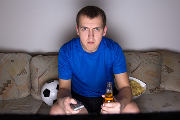 football supporter in uniform sitting on the sofa and watching t