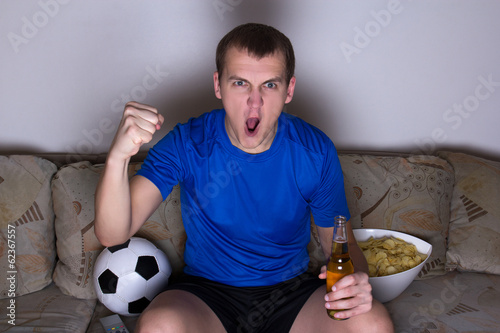 funny man watching football on tv and celebrating goal