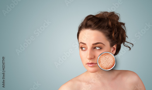 Beautiful young girl with magnifying glass of skin damage