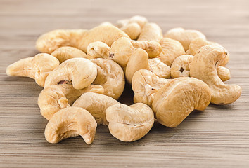A handful of row cashew nuts on wood background