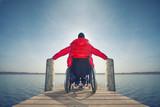 Fototapety junger Mann im Rollstuhl am See