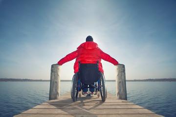 junger Mann im Rollstuhl am See