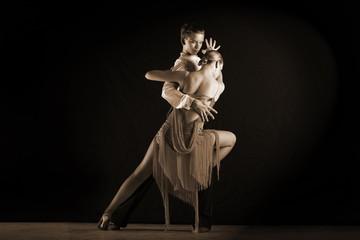 dancers in ballroom against on black