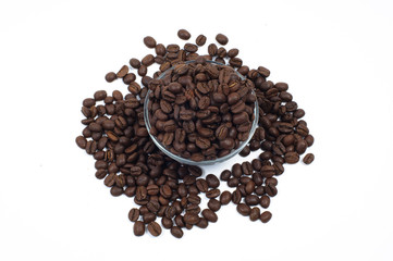 Scattered coffee beans around and within glass jug