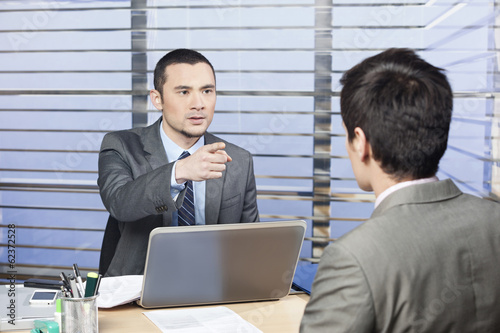 Young executive in the office criticize the team member