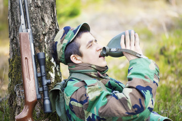 Recruit with water bottle in forest near tree