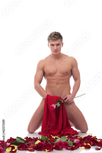 Sexy naked guy posing in studio with roses