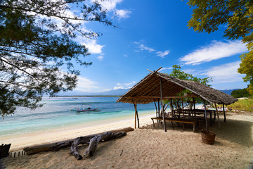 Traditional boat and bungalow on tropical beach