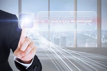 Businesswomans finger touching Danger button