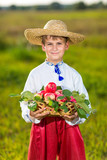 Happy farmer boy hold Organic Apples in Autumn Garden
