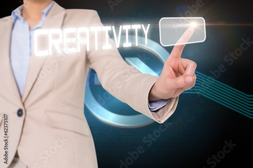 Businesswomans finger touching creativity button