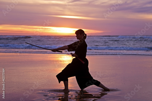 Young samurai women on the beach at sunset