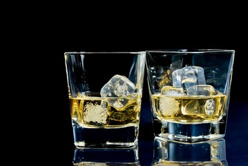 two glasses of alcoholic drink with ice on disco blue light