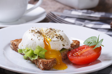 sandwich with open poached egg and coffee horizontal