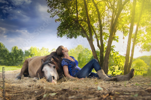 woman resting ,horse lying, outdoors under  tree in sunset