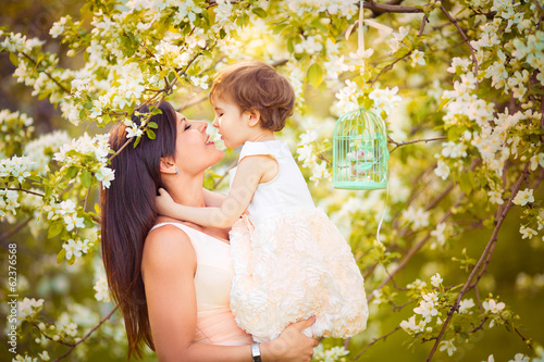 Happy woman and child in the blooming spring garden.Child kissi