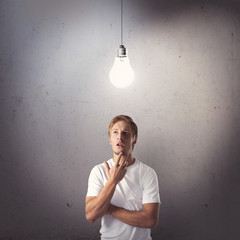 Portrait on thinking young man looking at light bulb