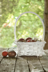 Easter eggs in white basket on old wooden table