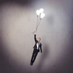 young businessman flying with light bulbs