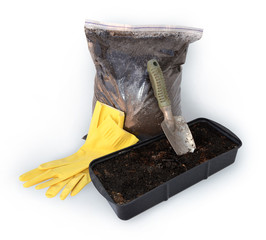 Gardening trowel, gloves, bag with peat and container for seedli