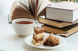 Cup of tea, cake and some books to read lying on the table