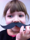 child with paper mustaches