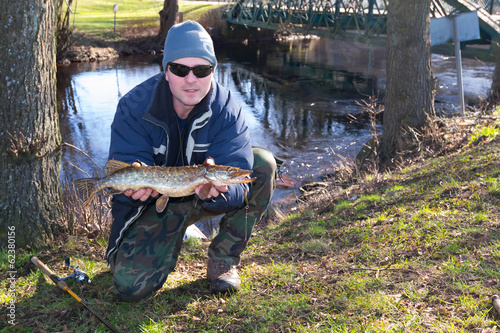 Angler with pike trophy from spring river
