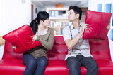Angry couple on red sofa at home