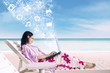 Asian female surfing online using laptop at beach