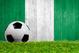 Soccer ball on grass with Nigeria flag background