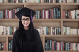 Beautiful female graduate smiling at library