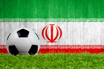 Soccer ball on grass with Iran flag background
