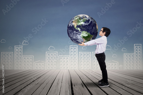 Boy holding the planet earth