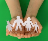 children's hands holding a paper human family