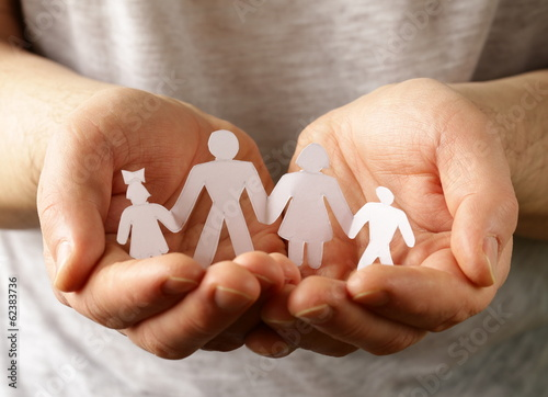 male hands holding a paper human family
