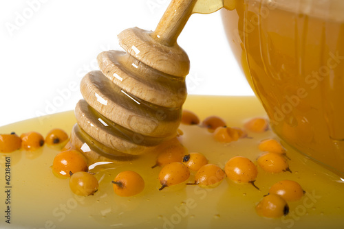 honey in the stick of honey on the bowl