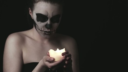 Low key footage of young woman with skull make-up.