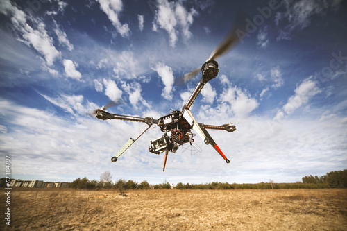 Tuinposter Helicopter Quadrocopter drone flying in the sky