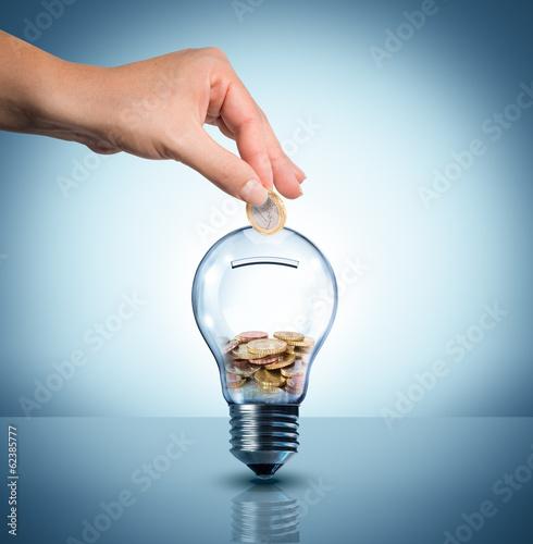 Leinwanddruck Bild invest to energy concept - euro in bulb - piggybank
