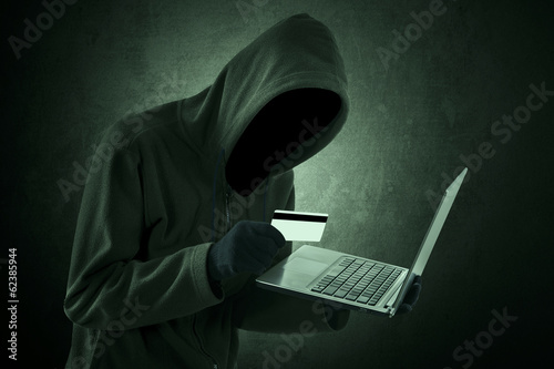 Man holding credit card with laptop