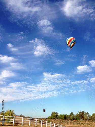 canvas print picture Beautiful hot air balloons in the sky over the countryside.