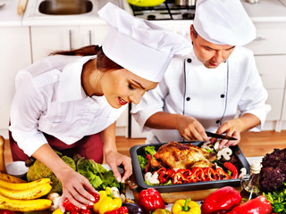 Man and woman in chef hat cooking chicken