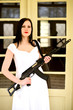 Young woman in a wedding dress with gun
